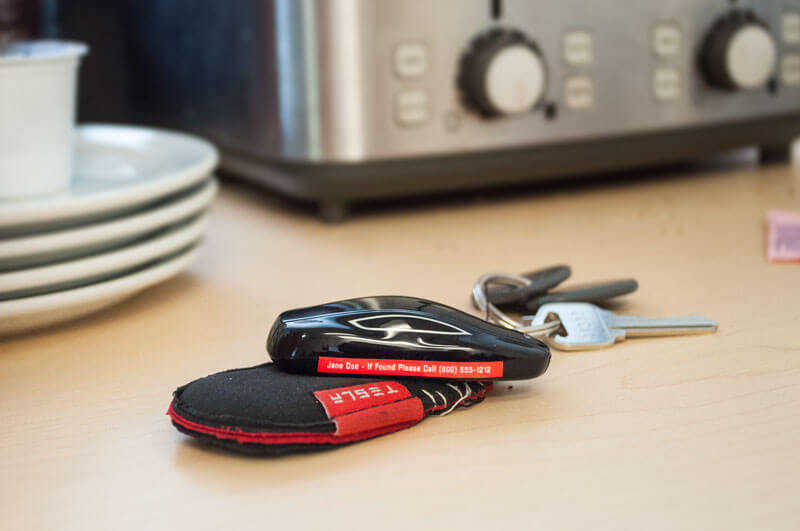 Tesla key fob with red IDmyStuff label left in kitchen